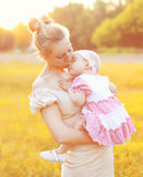 Sunny portrait of happy mom kissing baby on hands. In sunny evening with sunset Royalty Free Stock Photos