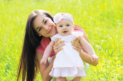 Sunny portrait of happy young mother with baby on the grass royalty free stock photos