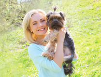 Sunny portrait of happy young woman owner with yorkshire terrier Royalty Free Stock Image