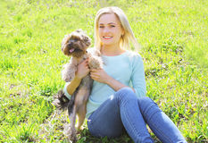 Sunny portrait of happy young woman owner with yorkshire terrier Stock Photography