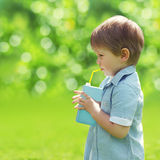 Sunny portrait of a little child drinking from a straw juice Royalty Free Stock Images