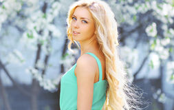 Sunny portrait lovely blonde girl in spring garden Stock Images