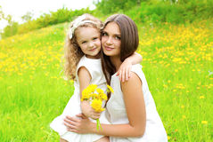 Sunny portrait of mother and daughter together with yellow flowers Royalty Free Stock Image