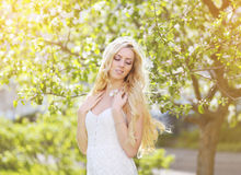 Sunny portrait pretty blonde girl eyes closed enjoying. Sunny spring garden, freshness, spring, nature - concept stock images