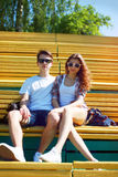 Sunny portrait of stylish young carefree couple sitting in park Royalty Free Stock Photos