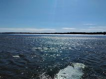 Sunny reflection on a river. With the shore on the horizon in the Quebec Canada region royalty free stock image