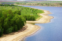 Sunny river beach with green trees Royalty Free Stock Image