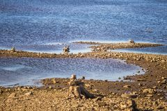 Sunny riverside landscape of a dried river bed and rocks. Stone balancing constructions near the river. Royalty Free Stock Photography