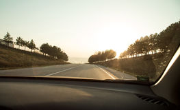 Sunny road from car window. Royalty Free Stock Images