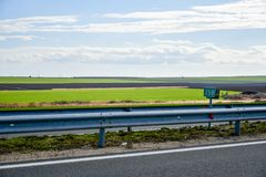 Sunny road. Empty  sunny road  with green field and blue heavy cloudly  sky in the morning Royalty Free Stock Photos
