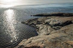 Sunny rocks in the ocean shore. Sunny rocks in the icy ocean shore Royalty Free Stock Photo
