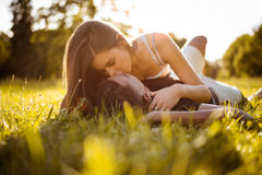 Sunny romance - young couple kissing in grass Stock Image