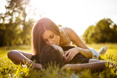 Sunny romance - young couple kissing in grass Royalty Free Stock Photo