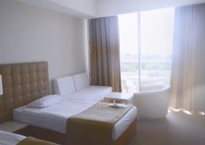 Sunny room in the hotel in light colors with two beds royalty free stock images
