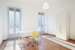 Sunny room studio with desk and chair Royalty Free Stock Photo