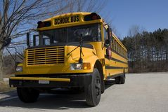Sunny School Bus. A yellow North American school bus stands in a parking lot in early spring royalty free stock photos