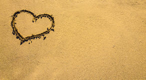 Sunny sea love sign on sand. The symbol of heart is drawn on sand. Royalty Free Stock Photography