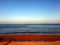 Sunny Seaside Scene con le barche a vela sull'orizzonte immagine stock