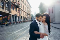 Sunny sensitive wedding portrait. Tenderly hugging beautiful couple of newlyweds in the town street. Sunny sensitive wedding portrait. Tenderly hugging Royalty Free Stock Images