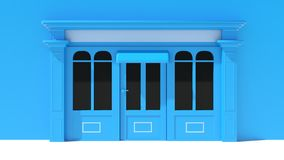 Sunny Shopfront with large windows White and blue store facade with awnings Stock Photos