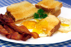 Sunny Side Eggs, Bacon and Toast. Sunny side eggs with one piece of fresh toast dipped into the egg yold,  A side of crisp bacon completes this appetizing image Stock Photos
