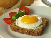 Sunny side up egg on a slice of bread. With tomatoes on a plate with a French loaf in the background Royalty Free Stock Photos