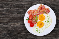 Sunny Side Up Eggs with crispy bacon. Sunny Side Up Eggs with crispy fried bacon, arugula and tomatoes on white plate on old dark wooden table, view from above Royalty Free Stock Image