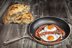 Sunny Side Up Eggs Fried With Bacon Rashers In Old Frying Pan Set On Old Weathered Garden Table With Pitta Bread Loaf Torn Halves Royalty Free Stock Photo
