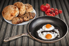 Sunny Side Up Eggs Fried in Old Frying Pan Set On Bamboo Mat With Baguette And Pitta Bread Loaves With Bunch Of Cherry Tomatoes Stock Photography