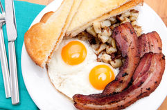 Sunny side up eggs with organic bacon Stock Photos