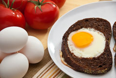 Sunny side up eggs in  toast. Eggs sunny side up in a slice of bread accomapnied by bowl of eggs and tomatoes Royalty Free Stock Photos