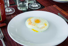 Sunny side up fried egg on white plate Royalty Free Stock Photos
