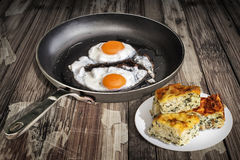 Sunny Side Up Fried Eggs in de Oude Bradende Plakken van de Pasteizeljanica van Pan With Plateful Of Cheese en van de Spinazie di royalty-vrije stock foto