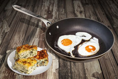 Sunny Side Up Fried Eggs in de Oude Teflon Bradende die Pan With Plateful Of Cheese-Plakken van Pasteigibanica op Oude Gebarsten  royalty-vrije stock afbeeldingen