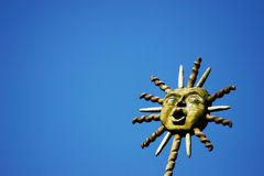 Sunny skies. Decorative sun mask held up to the blue sky Royalty Free Stock Images