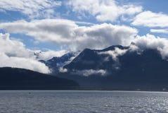 Sunny sky above mountains by ocean in Seward, Alaska royalty free stock photos