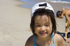 Sunny Smile. Little asian girl smiles at the beach with her white cap on backwards stock image