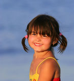 Sunny Smile. Little girl smiling at the beach in summer, wearing a red and yellow swimming costume and with her hair in pigtails Royalty Free Stock Image