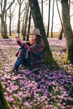 Spring crocuses in forest and a female traveler. Sunny smiling girl taking selfie of surrounding beauty, good mood, trying to catch some fresh air for later too Stock Photography