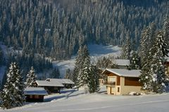 A sunny snow covered landscape of woods and cottages in the mountainside village of Beatenberg in Switzerland. At Christmas time stock photo