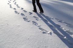 Sunny snow shoe prints with a man stock image