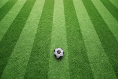 Sunny soccer field with ball Royalty Free Stock Image