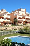 Sunny Spanish Apartment Block. Sunny and compact apartment block on Spanish urbanisation with swimming pool and gardens Royalty Free Stock Photography