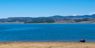Panoramic view of lake Batak Pazardzhik, Bulgaria. Sunny spring day, clear skyies, great lake and old fisherman Boat ready to be taken out Royalty Free Stock Image