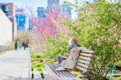 Sunny spring day on New York`s High Line. Little girl enjoy early spring in the city outdoors. The High Line is a popular linear park built on the elevated train Stock Photography