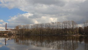 Sunny spring day, the river on the outskirts of the city. White clouds on the blue sky reflected in the water stock footage