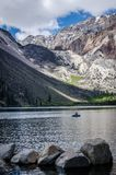 Single boater in a dingy boat on Convict Lake in California. Sunny spring day, rocks in the foreground of the Sierra Nevada high alpine lake royalty free stock image