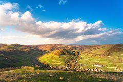 Sunny spring day. Village in green mountain valley Stock Images