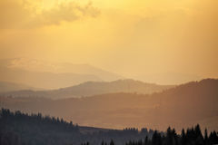 Sunny spring evening in mountain village. Fields and hills Royalty Free Stock Photo