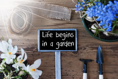 Sunny Spring Flowers, Sign, Quote Life Begins In A Garden Stock Photos